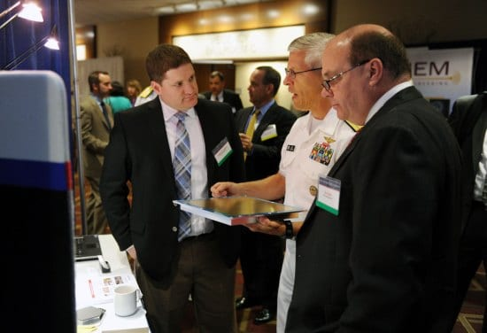 Rear Adm. Matthew Klunder talks with Randall Lapierre and Donald Flodin of SI2 Technologies at the 2014 Navy Opportunity Forum, Arlington, VA, June 2, 2014